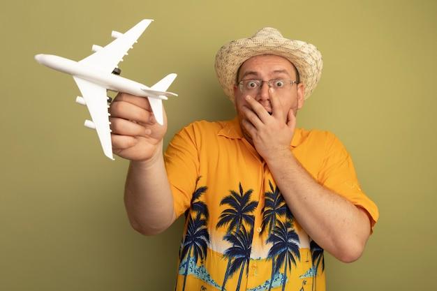 녹색 벽 위에 서있는 손으로 입을 덮고 충격을 받고 장난감 비행기를 들고 여름 모자에 주황색 셔츠를 입고 안경에 남자