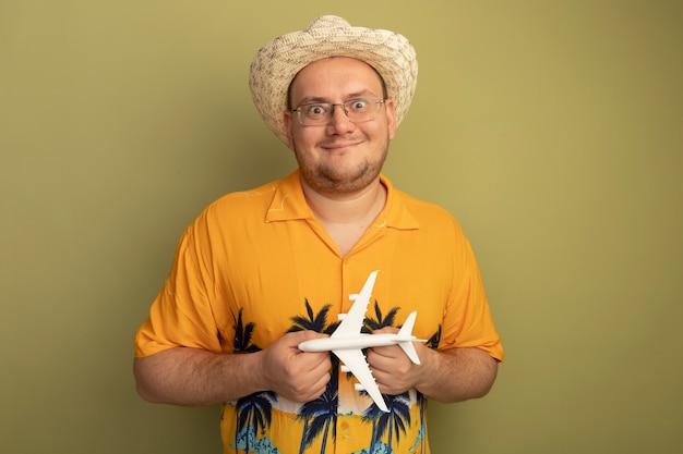 녹색 벽 위에 행복하고 긍정적 인 미소 서 장난감 비행기를 들고 여름 모자에 주황색 셔츠를 입고 안경 남자