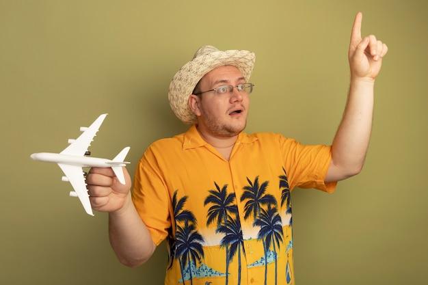 여름 모자에 주황색 셔츠를 입고 안경에 남자가 옆으로 집게 손가락을 보여주는 녹색 벽에 놀란 행복 서를 보여주는 장난감 비행기를 들고