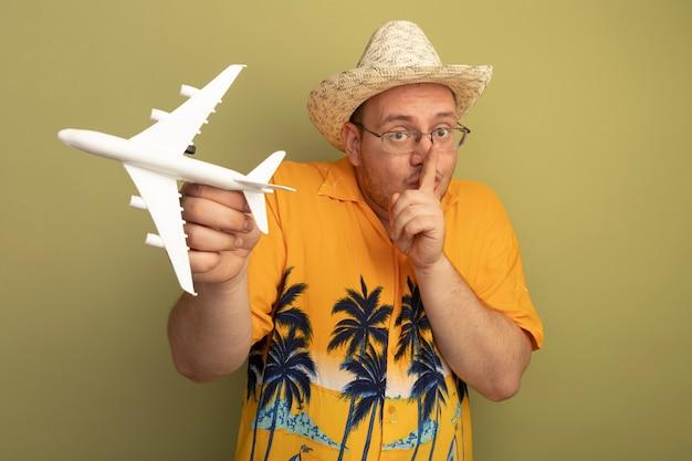 녹색 벽 위에 서있는 입술에 손가락으로 침묵 제스처를 만드는 장난감 비행기를 들고 여름 모자에 주황색 셔츠를 입고 안경 남자
