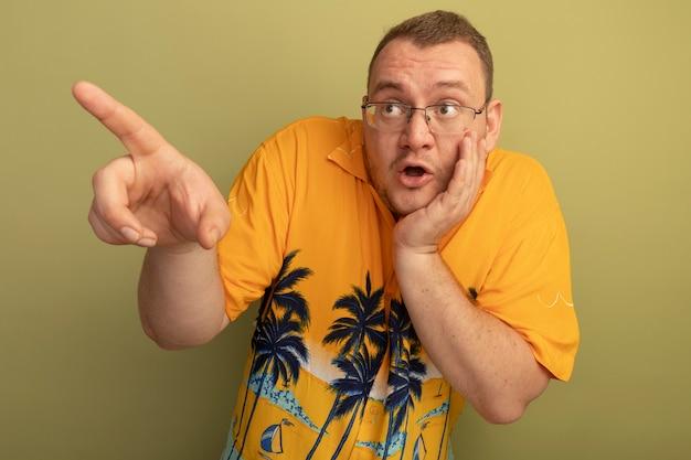 明るい壁の上に立って混乱している何かを指で指して脇を見てオレンジ色のシャツを着た眼鏡の男