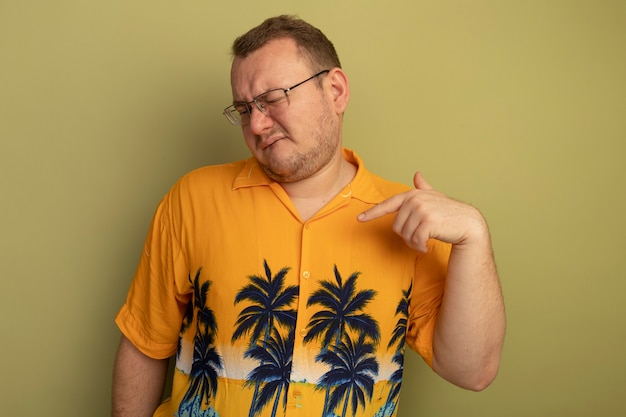 オレンジ色のシャツを着た眼鏡をかけた男が、明るい壁の上に立っている自分を指で指さして混乱し、不快に見えます