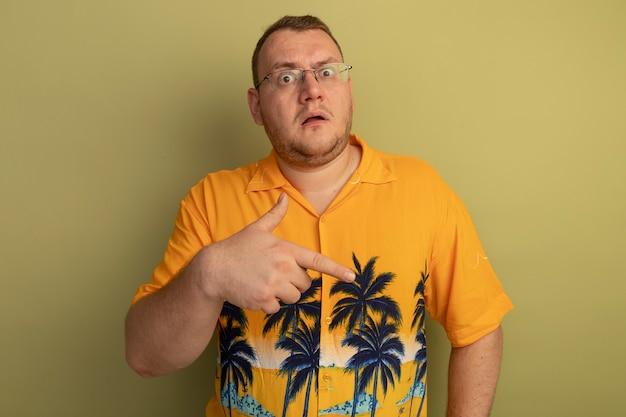 明るい壁の上に立っている側に指で指している混乱しているように見えるオレンジ色のシャツを着た眼鏡の男
