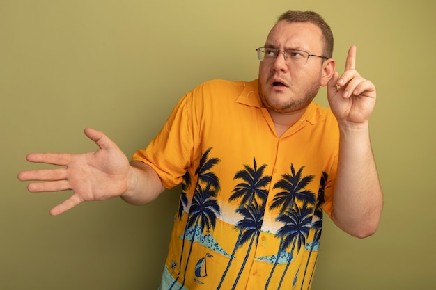 開いた手のひらと人差し指が明るい壁の上に立っていることを示して混乱しているように見えるオレンジ色のシャツを着た眼鏡の男