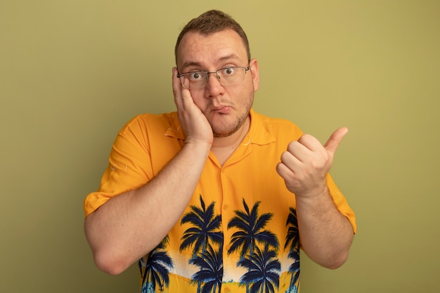 混乱しているように見えるオレンジ色のシャツを着た眼鏡の男は、明るい壁の上に立って混乱している親指を示しています