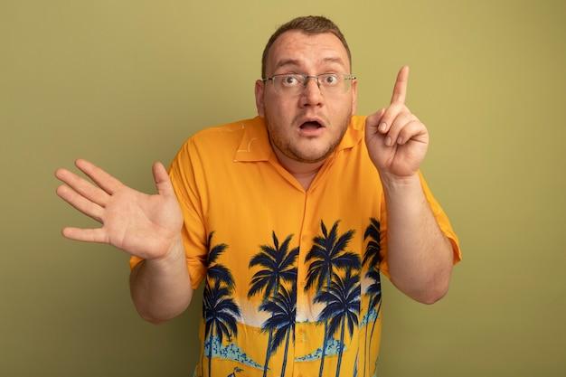 明るい壁の上に立っている人差し指を示して驚いて見えるオレンジ色のシャツを着た眼鏡の男