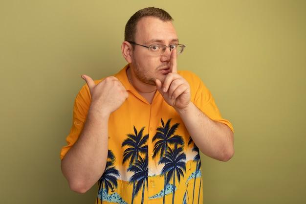 明るい壁の上に立っている唇に指で沈黙のジェスチャーをするオレンジ色のシャツを着た眼鏡の男