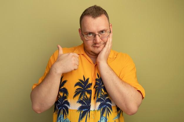 明るい壁の上に立って笑顔で親指を示すオレンジ色のシャツを着た眼鏡の男