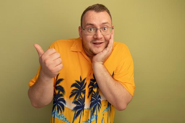 明るい壁の上に立っている親指で元気に後ろを指して笑顔のオレンジ色のシャツを着た眼鏡の男