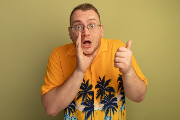 オレンジ色のシャツを着た眼鏡の男は、明るい壁の上に立っている口の近くで手をつないで後ろを向いて驚いた