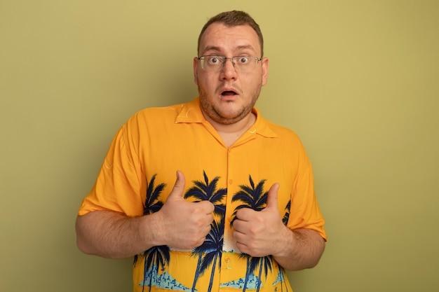 オレンジ色のシャツを着た眼鏡の男は、明るい壁の上に立って親指を見せて驚いた