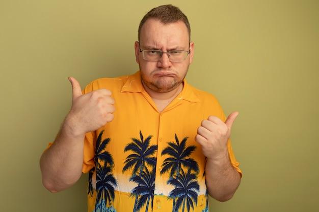明るい壁の上に立って親指を見せて眉をひそめている怒っている顔とオレンジ色のシャツを着ている眼鏡の男