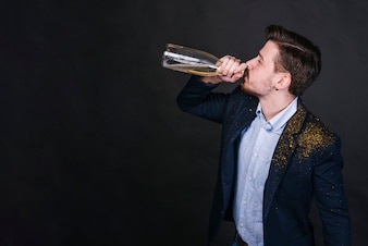 Man in glitter powder drinking champagne from bottle