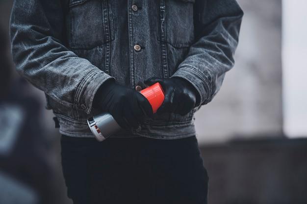 Мужчина в перчатках и джинсовой куртке берет аэрозольную краску. серые дни работы художников-граффити