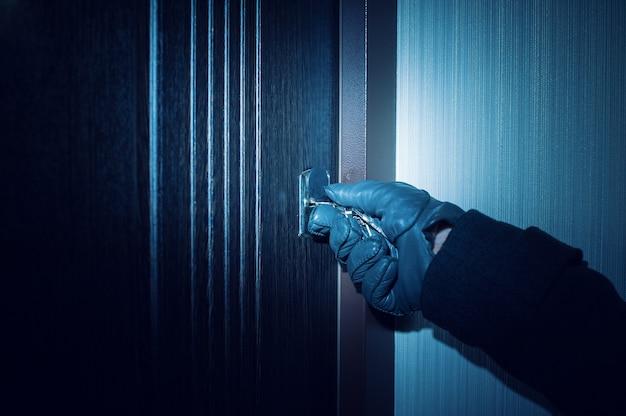 手袋をはめた男がドアを開ける