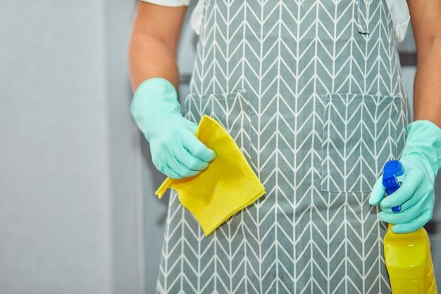 手に掃除用品、ぼろきれ、消毒スプレーボトルを持った手袋をはめた男。ジェンダーの固定観念を打ち破る、ジェンダーニュートラルな家庭の概念