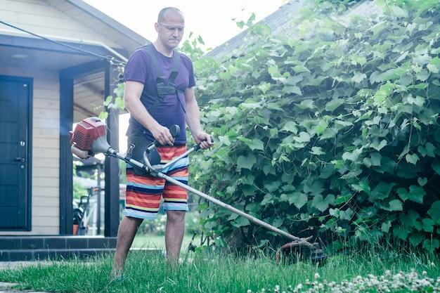 ゴーグル、ショートパンツ、tシャツを着た男が、ブドウ園と家の入り口を背景に、ガソリントリマーで芝生を刈り取ります