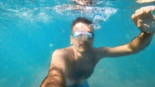 지중해 바다의 푸르고 투명한 물 아래에서 수영하는 고글을 쓴 남자. 카메라를 들고