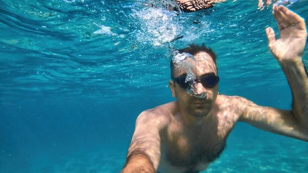 地中海の青く透明な水の下で泳ぐゴーグルの男。カメラを持って
