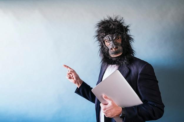 Человек в маске гориллы с ноутбуком под мышкой и указывая пальцем в сторону