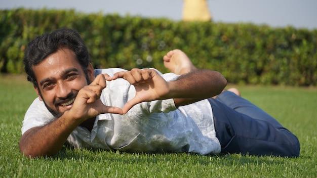 Человек в траве и улыбается Premium Фотографии