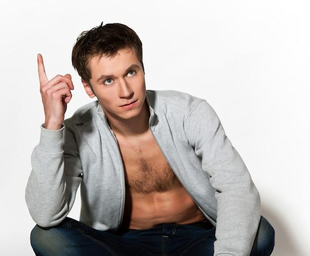 Мужчина в сером пиджаке и джинсах позирует, сидя с поднятой правой рукой и задумавшись над пальцем