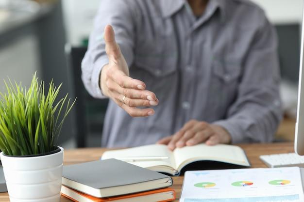 Человек в серой рубашке дать руку как привет в офисе крупным планом. друг добро пожаловать посредничество предложение позитивное вступление спасибо жест саммит участие одобрение мотивация мужчина рука удар сделка