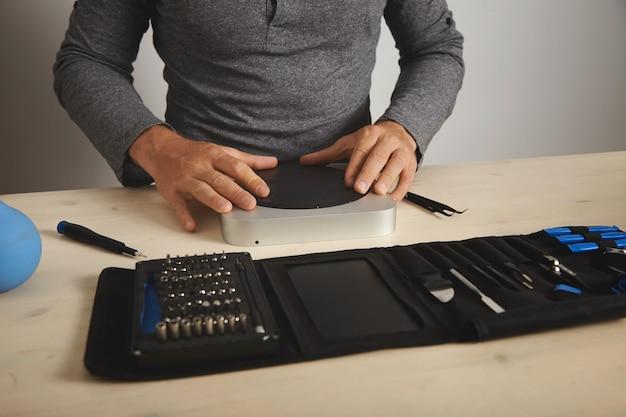 灰色のtシャツを着た男が、修理したコンピューターを閉じ、テーブルの上の彼の前にある道具