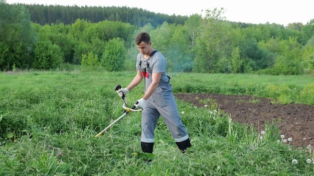 회색 작업복을 입은 남자가 들판에서 트리머로 쐐기풀을 깎는다