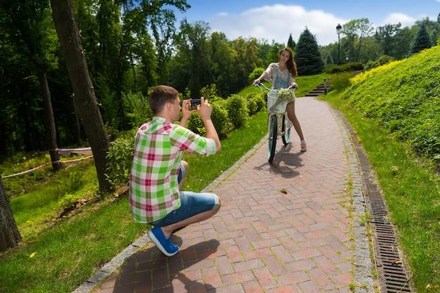 Мужчина в красно-зеленой клетчатой рубашке фотографирует свою девушку, сидящую на велосипеде с букетом маленьких белых цветов в корзине в парке