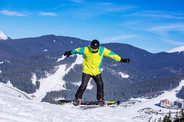 スノーボードでジャンプする緑のコートを着た男。冬の山の旅