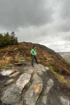 Человек в зеленой куртке стоит на вершине холма, любуясь пейзажем в горах уиклоу