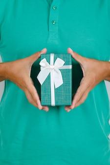 プレゼントボックス、正面図を保持している緑のtシャツの男。