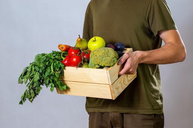 Человек в зеленой футболке держит деревянную коробку, полную овощей