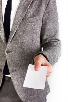 Человек в сером деловом костюме держит белую карточку в руке