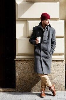 Человек в сером пальто стоит с чашкой кофе снаружи