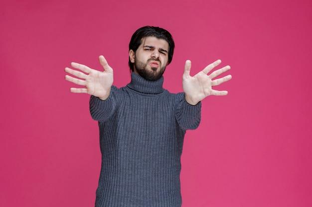 灰色のシャツを着た男は、何かを恐れたり、拒否したりします。