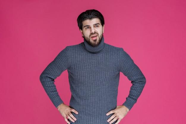 Мужчина в серой рубашке держится за руки на талии, как будто у него болит спина.