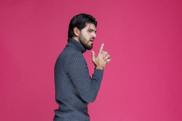손에 총 기호를 만드는 회색 셔츠에 남자.