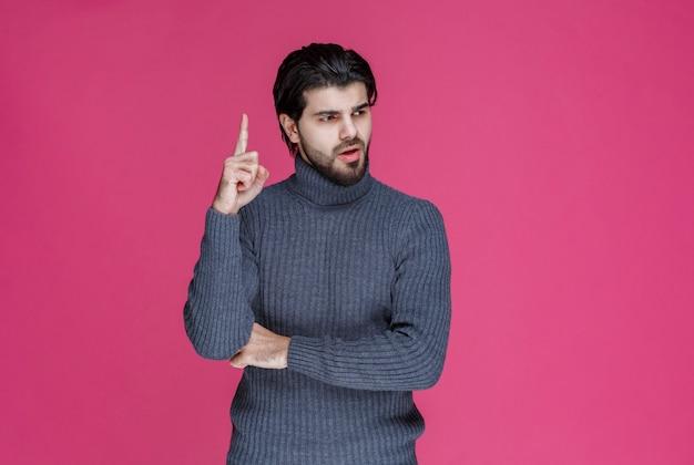 人差し指を使って何かを指さしたり、誰かを紹介したりする灰色のセーターを着た男。