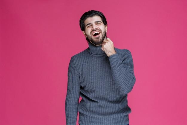 彼の拳を示し、力強く感じる灰色のセーターを着た男。