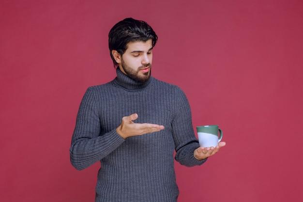 커피 잔을 들고 그것을 가리키는 회색 스웨터에 남자.