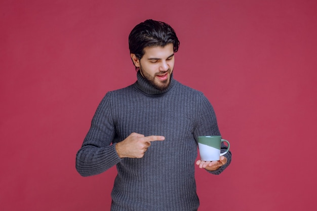Человек в сером свитере, держа кружку кофе и указывая на нее.