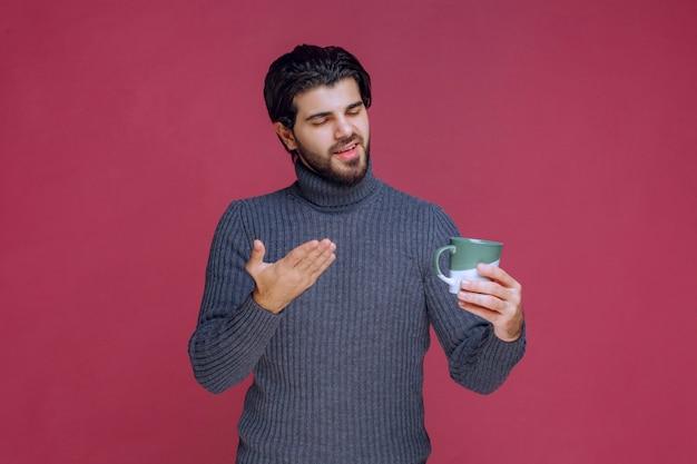 커피 잔을 들고 그것을 가리키는 회색 스웨터에 남자. 무료 사진