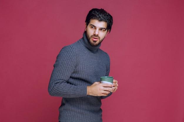 手にコーヒーマグを持っている灰色のセーターの男。 無料写真