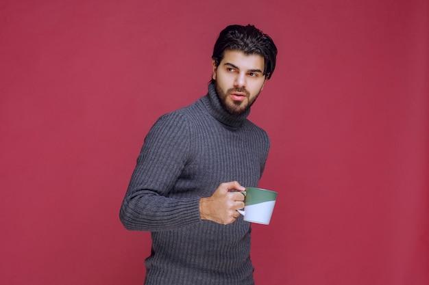 커피 잔을 손에 들고 회색 스웨터에 남자.