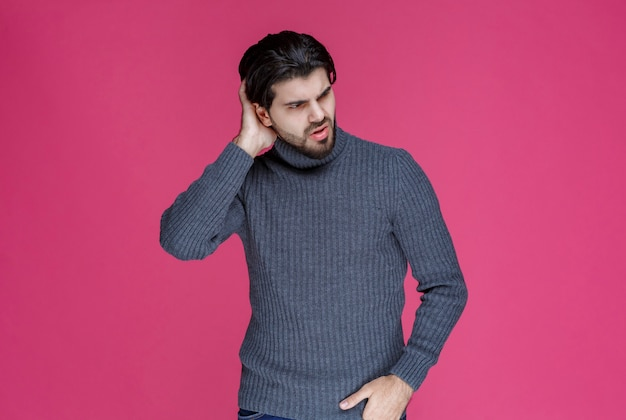 Мужчина в сером свитере держит ухо, так как ему трудно слушать.
