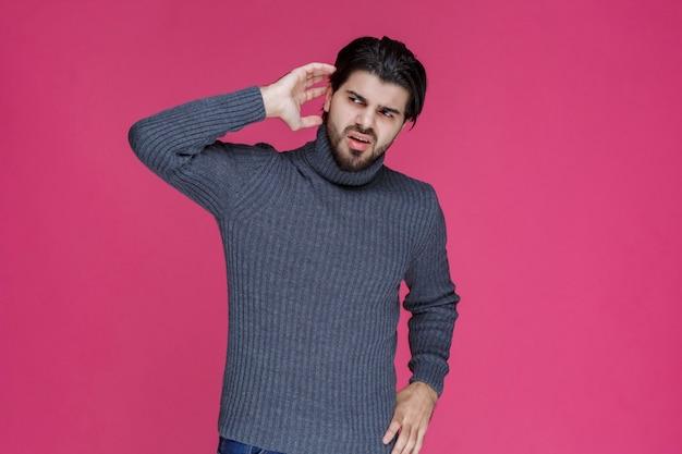 彼は聞くのに苦労しているので彼の耳を保持している灰色のセーターの男。