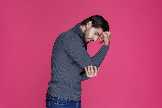 그의 머리를 잡고 회색 스웨터에 남자와 두통