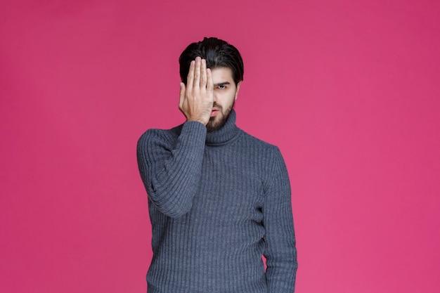 Мужчина в сером свитере, глядя сквозь пальцы.